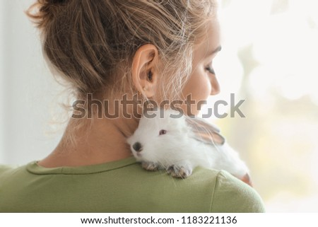 Beautiful young woman with cute rabbit at home