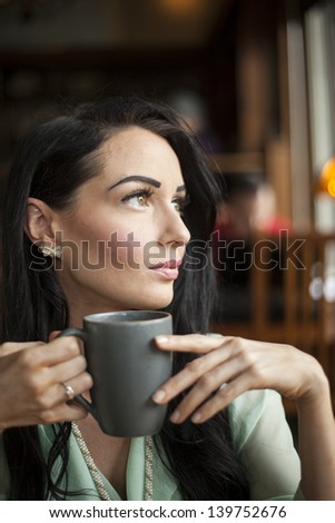 Beautiful young woman with dark brown hair and eyes holding a gray coffee cup.