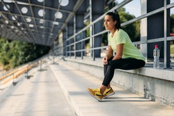 Beautiful young woman with dark hair sitting on stairs with bottle of water at stadium. Sporty female enjoying favorite hobby on fresh air.