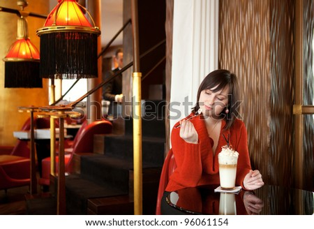 Beautiful young woman with delicious latte in cafe