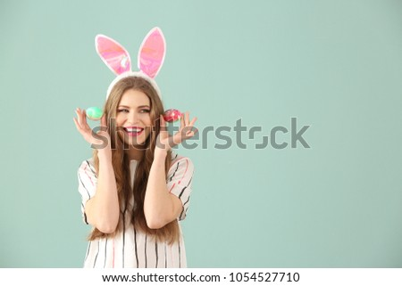 Beautiful young woman with Easter eggs and bunny ears on color background #1054527710