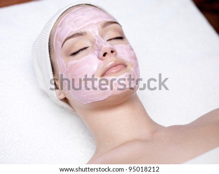 Beautiful young woman with facial mask in spa salon - indoors