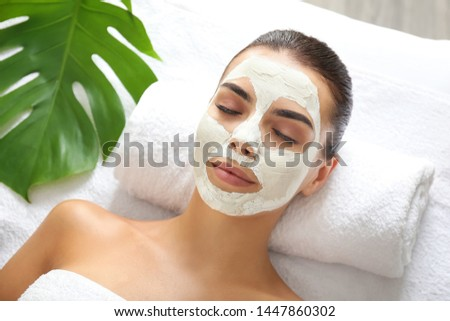 Beautiful young woman with facial mask relaxing in spa salon