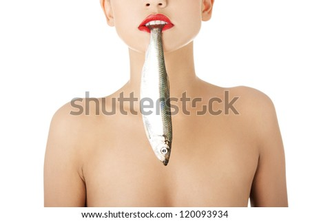 Beautiful young woman with fish in her mouth