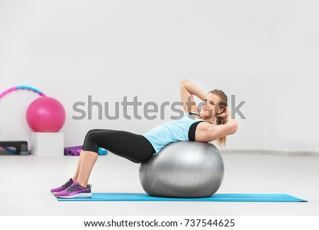Stock Photo Beautiful young woman with fitness ball training in gym
