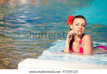 Beautiful young woman with flower resting in the pool of expensive hotel