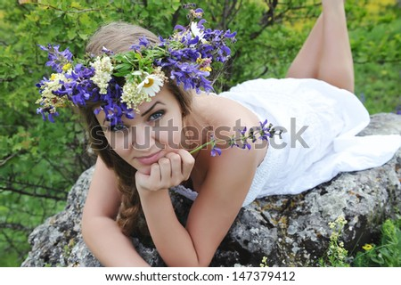 Beautiful young woman with flower wreath outdoors