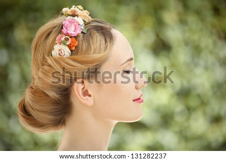 Beautiful young woman with flowers wreath in hair on natural green background
