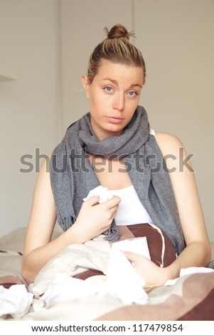 Beautiful young woman with flu feeling sorry for herself sitting in bed with a scarf around her neck and a toilet roll for tissues