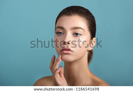 Beautiful young  woman with fresh clean perfect skin. Portrait of beauty model with natural make up and and hand with manicure touching face. Spa, skincare and wellness. #1186541698