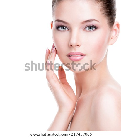 Beautiful young woman with fresh clean skin that touches her face with a hand -  isolated on white.