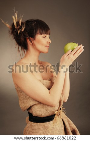 Beautiful young woman with fresh green apple. Nature concept.