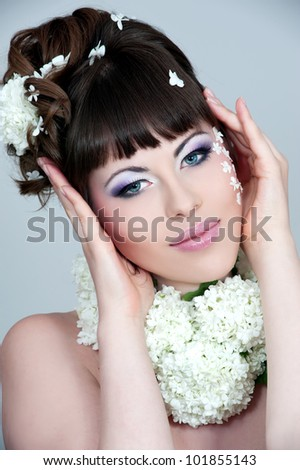 Beautiful young woman with fresh spring flowers in her hair