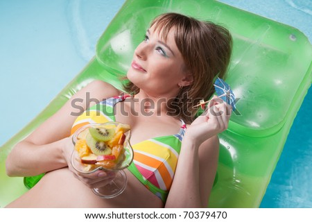 Beautiful young woman with fruit salad  lies  on an inflatable mattress in the pool. Vacation.