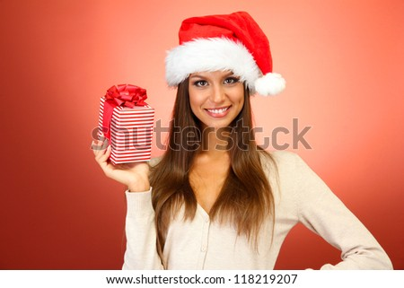 beautiful young woman with gift, on red background