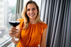Beautiful young woman with glass of red wine standing near window