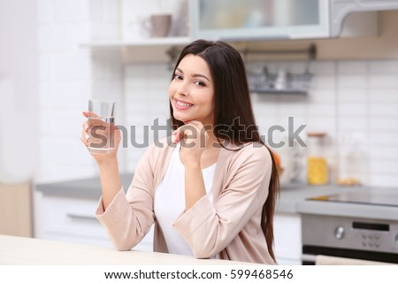 Beautiful young woman with glass of water in kitchen