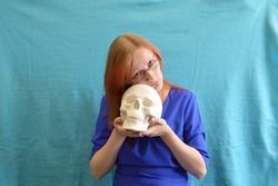 Beautiful young woman with glasses dressed in a blue dress with a sculpture in the shape of a skull in her hands.