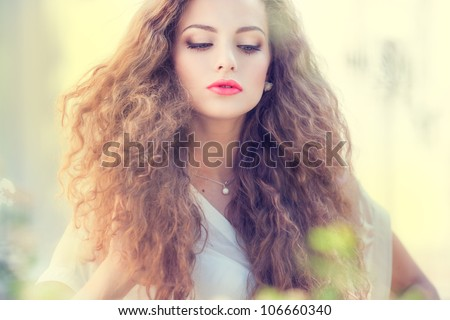 Beautiful young woman with gorgeous curly fair outdoors