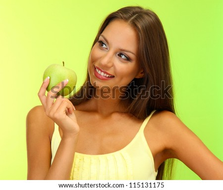 beautiful young woman with green apple, on green background