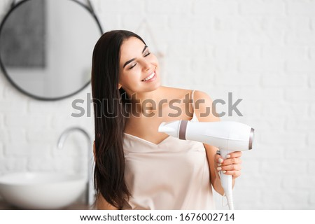Beautiful young woman with hair dryer in bathroom