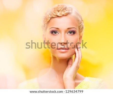Beautiful young woman with hairdo touching her face with hand - stock photo