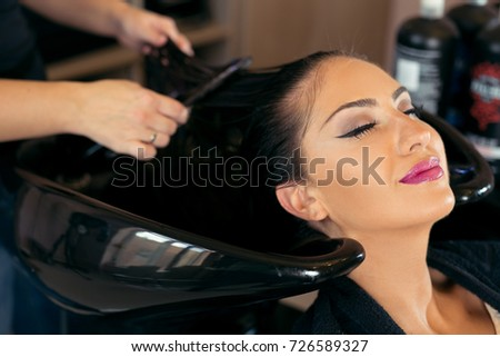 Beautiful young woman with hairdresser washing head at hair salon #726589327
