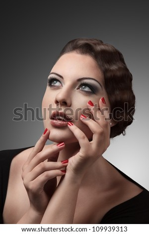 Beautiful young woman with hands over face retro style studio portrait