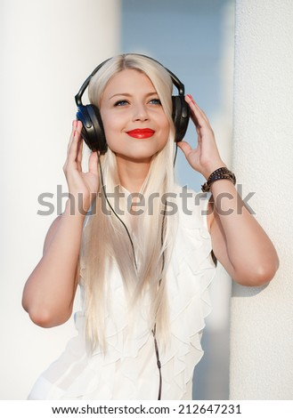 Beautiful young woman with headphones. Enjoy music outdoors.