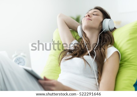 Beautiful young woman with headphones relaxing on the bed, she is listening to music using a tablet, chill out and leisure concept