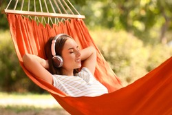 Beautiful young woman with headphones resting in hammock outdoors