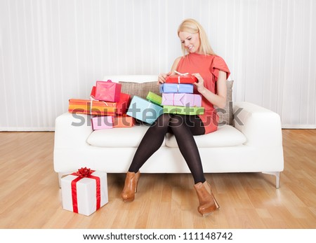 Beautiful young woman with her presents on the sofa