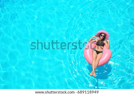 Beautiful young woman with inflatable ring relaxing in blue swimming pool #689118949