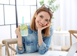 Beautiful young woman with lemonade and laptop in cafe