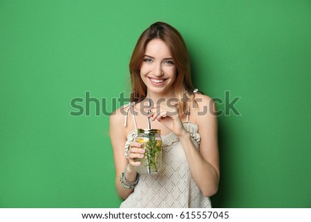 Beautiful young woman with lemonade on color background