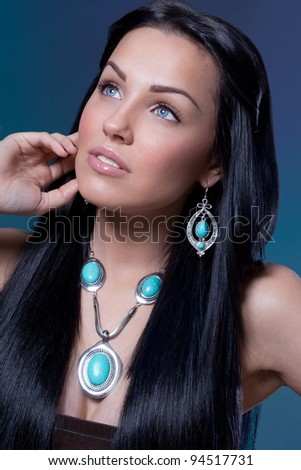 Beautiful young woman with long black hair posing in jewelry