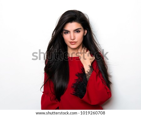 beautiful young woman with long black hair posing on grey background in red dress