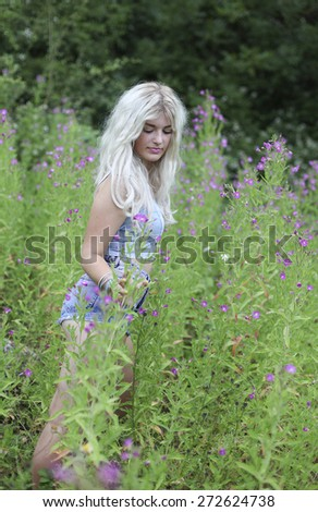 Beautiful young woman with long blonde hair in long grass