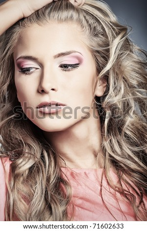 Beautiful young woman with long blonde hair posing over grey background. - stock photo
