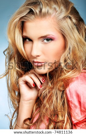 Beautiful young woman with long blonde hair posing over grey background.