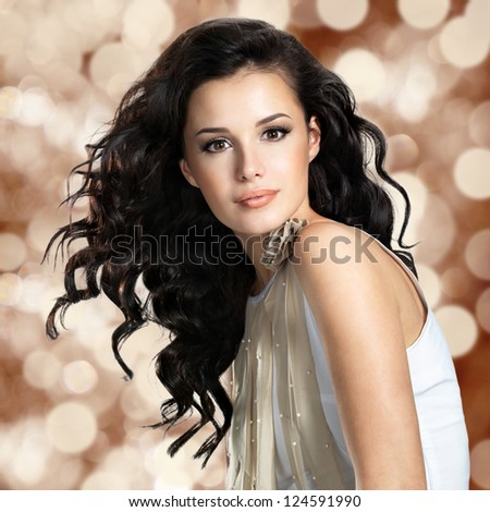 Beautiful young woman with long brown hair. Pretty model poses at studio. Blinking Background. Bokeh