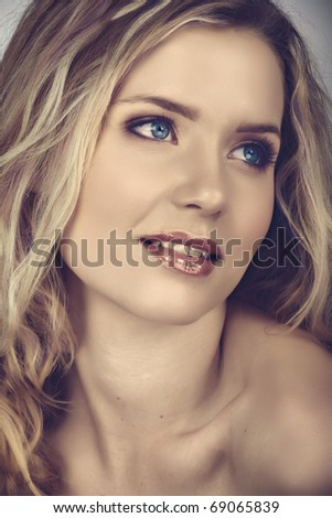 beautiful young woman with long curly blond hair and natural make-up smiling happily with cross process effect from 16 Bit RAW