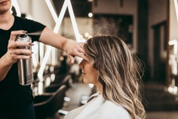 Beautiful young woman with long curly hair in hair salon. Professional hairdresser styling with hairspray.