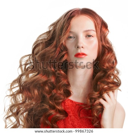 Beautiful young woman with long curly hair in red light - stock photo