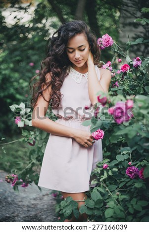 Beautiful young woman with long curly hair posing near roses in a garden