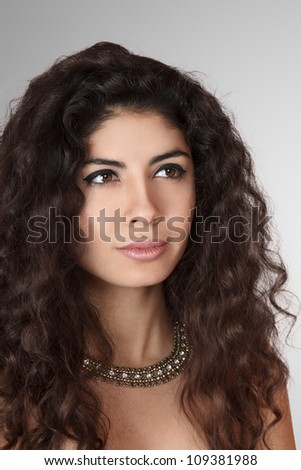 Beautiful young woman with long curly hair studio portrait