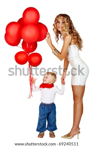 beautiful young woman with long curly hair wearing party sequin minidress and gold shoes playing with a little boy in jeans holding bunch of red balloons.