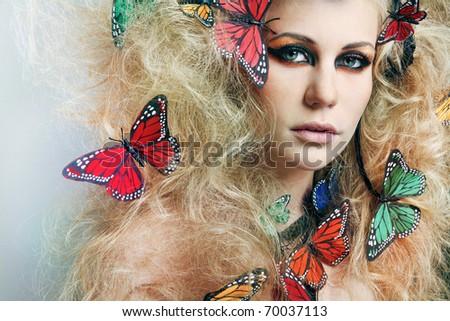 Beautiful young woman with long curly hair with butterflies.