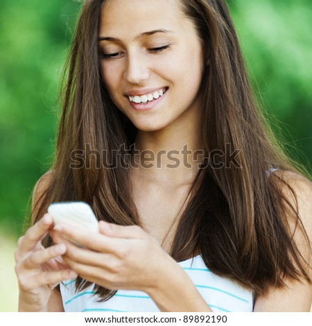 beautiful young woman with long dark hair looks down hands holding phone - stock photo