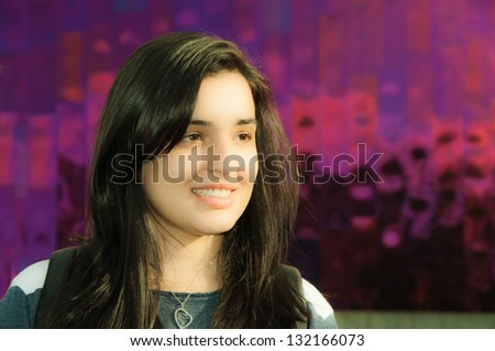 Beautiful Young Woman with long dark hair.  Purplish red metallic background.  Copy space.